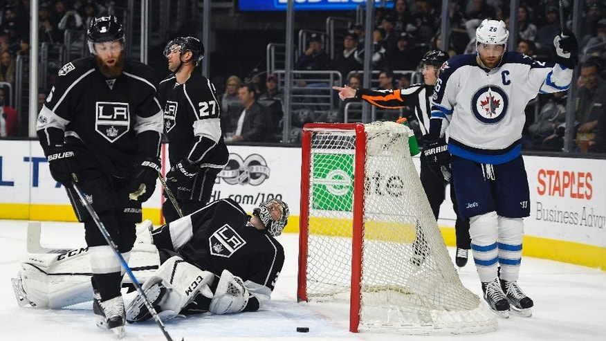 Winnipeg Jets right wing Blake Wheeler, right, celebrates a goal by right wing Patrik Laine, of Finland, as Los Angeles Kings goalie Ben Bishop lies on the ice as defenseman Jake Muzzin, left, and defenseman Alec Martinez skate away during the first period of an NHL hockey game, Thursday, March 23, 2017, in Los Angeles. (AP Photo/Mark J. Terrill)