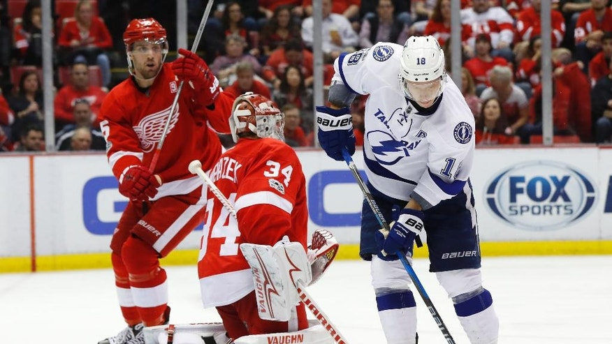 Tampa Bay Lightning left wing Ondrej Palat (18) shoots to score on Detroit Red Wings goalie Petr Mrazek (34) in the third period of an NHL hockey game Friday, March 24, 2017, in Detroit. (AP Photo/Paul Sancya)