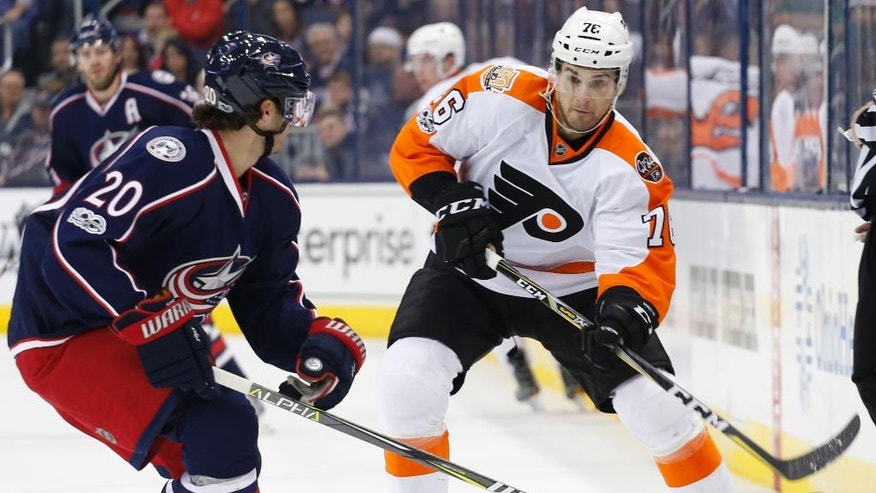 Philadelphia Flyers' Chris VandeVelde, right, dumps the puck past Columbus Blue Jackets' Brandon Saad during the first period of an NHL hockey game, Saturday, March 25, 2017, in Columbus, Ohio. (AP Photo/Jay LaPrete)