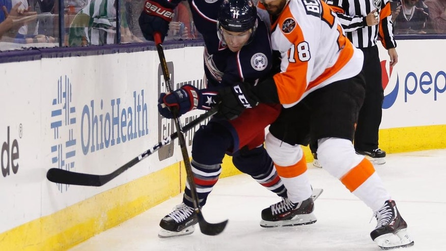Columbus Blue Jackets' Matt Calvert, left, and Philadelphia Flyers' Pierre-Edouard Bellemare, of France, fight for a loose puck during the second period of an NHL hockey game, Saturday, March 25, 2017, in Columbus, Ohio. (AP Photo/Jay LaPrete)