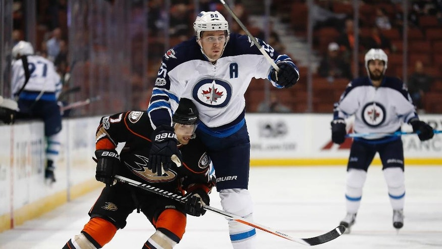 Anaheim Ducks left wing Andrew Cogliano, left, and Winnipeg Jets center Mark Scheifele, center, vie for the puck during the first period of an NHL hockey game, Friday, March 24, 2017, in Anaheim, Calif. (AP Photo/Ryan Kang)