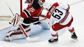 Carolina Hurricanes left wing Jeff Skinner (53) scores a goal on New Jersey Devils goalie Cory Schneider during the third period of an NHL hockey game, Saturday, March 25, 2017, in Newark, N.J. The Hurricanes won 3-1. (AP Photo/Julio Cortez)