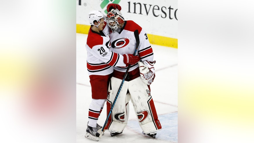 Carolina Hurricanes right wing Sebastian Aho, left, of Finland, and goalie Eddie Lack, of Sweden, celebrate after defeating the New Jersey Devils 3-1 during an NHL hockey game, Saturday, March 25, 2017, in Newark, N.J. (AP Photo/Julio Cortez)
