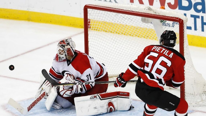 Carolina Hurricanes goalie Eddie Lack, of Sweden, stops a shot by New Jersey Devils left wing Blake Pietila during the third period of an NHL hockey game, Saturday, March 25, 2017, in Newark, N.J. The Hurricanes won 3-1. (AP Photo/Julio Cortez)