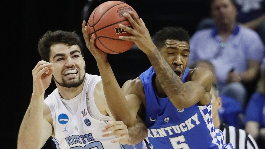 Kentucky guard Malik Monk grabs a loose ball in front of North Carolina forward Luke Maye in the first half of the South Regional final game in the NCAA college basketball tournament Sunday