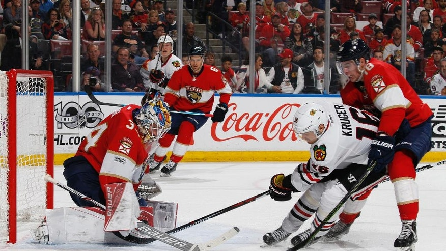 Florida Panthers goaltender James Reimer (34) stops a shot by Chicago Blackhawks center Marcus Kruger (16) as Florida Panthers right wing Reilly Smith (18) helps to defend during the second period of an NHL hockey game, Saturday, March 25, 2017, in Sunrise, Fla. (AP Photo/Joel Auerbach)
