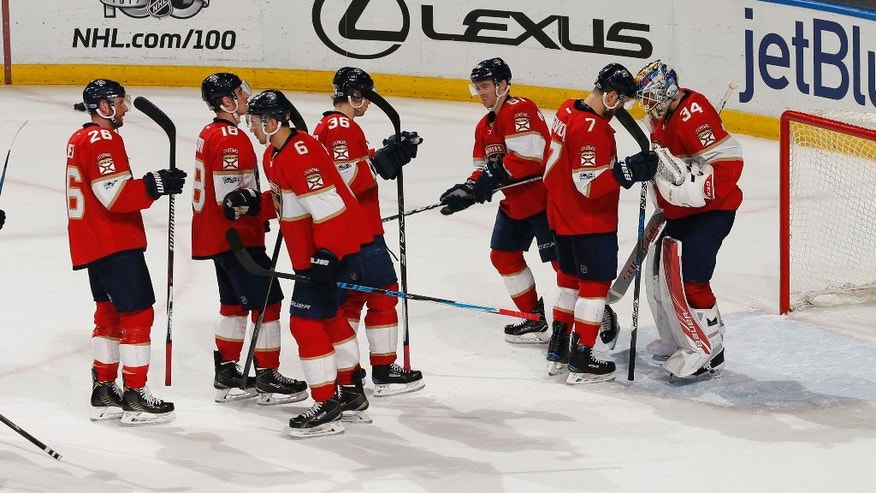 Florida Panthers goaltender James Reimer (34) is congratulated by teammates at the end of the third period of an NHL hockey game against the Chicago Blackhawks, Saturday, March 25, 2017, in Sunrise, Fla. The Panthers defeated the Blackhawks 7-0. (AP Photo/Joel Auerbach)