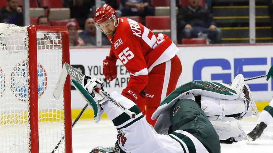 Minnesota Wild goalie Devan Dubnyk (40) falls after being hit by Detroit Red Wings defenseman Niklas Kronwall (55) in the second period of an NHL hockey game Sunday, March 26, 2017, in Detroit. (AP Photo/Paul Sancya)