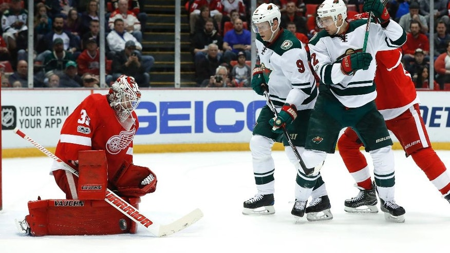 Detroit Red Wings goalie Jimmy Howard (35) stops a shot as Minnesota Wild center Mikko Koivu (9) and Nino Niederreiter (22) wait for the rebound in the first period of an NHL hockey game Sunday, March 26, 2017, in Detroit. (AP Photo/Paul Sancya)