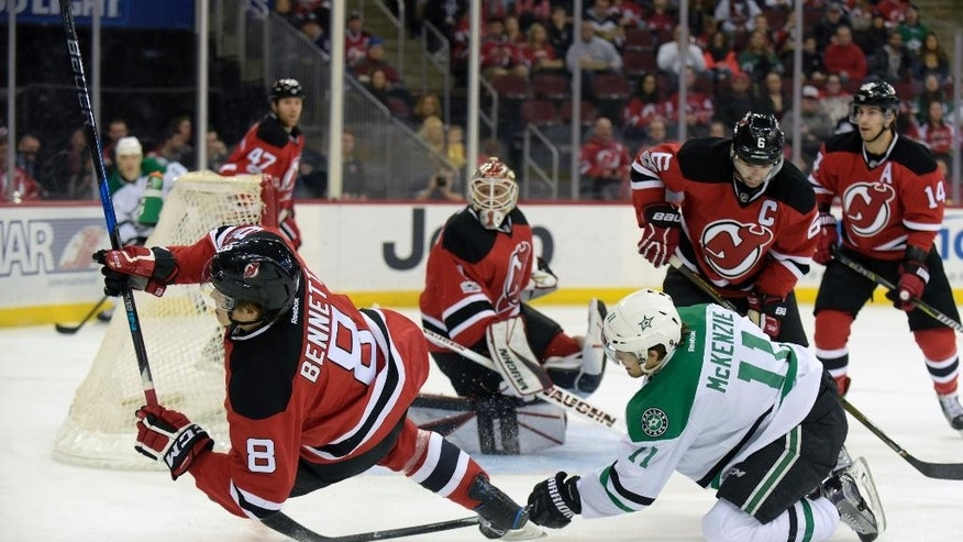 New Jersey Devils right wing Beau Bennett (8) is tripped by Dallas Stars left wing Curtis McKenzie (11) during the first period of an NHL hockey game Sunday, March 26, 2017, in Newark, N.J. (AP Photo/Bill Kostroun)