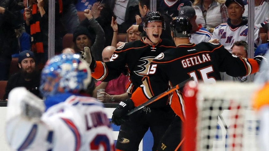 Anaheim Ducks defenseman Josh Manson, center, celebrates with center Ryan Getzlaf, right, after scoring a goal on New York Rangers goalie Henrik Lundqvist, left, during the second period of an NHL hockey game, Sunday, March 26, 2017, in Anaheim, Calif. (AP Photo/Ryan Kang)