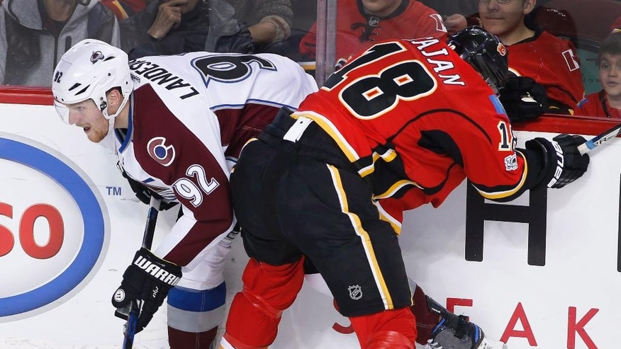 Colorado Avalanche's Gabriel Landeskog, left, from Sweden, is hit by Calgary Flames' Matt Stajan during second period NHL action in Calgary, Alberta, Monday, March 27, 2017. (Larry MacDougal/The Canadian Press via AP)
