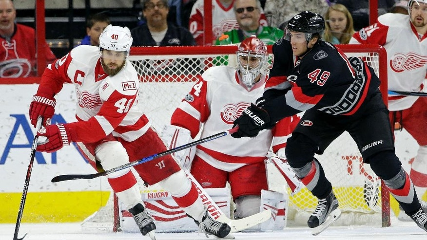 Detroit Red Wings' Henrik Zetterberg (40), of Sweden, controls the puck while Carolina Hurricanes' Victor Rask (49), of Sweden, chases in front of Red Wings goalie Petr Mrazek (34), of the Czech Republic, during the first period of an NHL hockey game in Raleigh, N.C., Monday, March 27, 2017. (AP Photo/Gerry Broome)