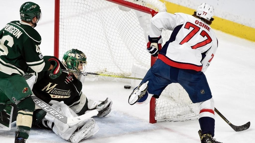 Washington Capitals right wing T.J. Oshie (77) scores a goal against Minnesota Wild defenseman Jared Spurgeon (46) and goalie Devan Dubnyk (40) during the first period of an NHL hockey game, Tuesday, March 28, 2017, in St. Paul, Minn. (AP Photo/Hannah Foslien)