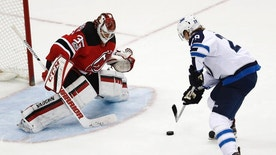 Winnipeg Jets right wing Patrik Laine (29), of Finland, prepares to score a goal on New Jersey Devils goalie Cory Schneider (35) during a shootout of an NHL game, Tuesday, March 28, 2017, in Newark, N.J. The Jets won 4-3. (AP Photo/Julio Cortez)