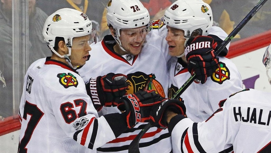 Chicago Blackhawks' Artemi Panarin (72) celebrates his goal with Tanner Kero (67) and Patrick Kane (88) in the first period of an NHL hockey game against the Pittsburgh Penguins in Pittsburgh, Wednesday, March 29, 2017. (AP Photo/Gene J. Puskar)