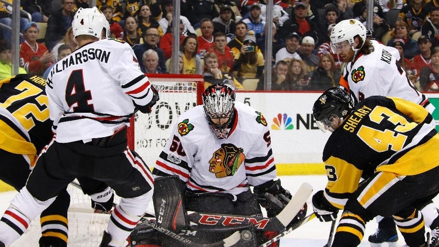 Chicago Blackhawks goalie Corey Crawford (50) stops a shot by Pittsburgh Penguins' Patric Hornqvist (72) in the second period of an NHL hockey game in Pittsburgh, Wednesday, March 29, 2017. (AP Photo/Gene J. Puskar)