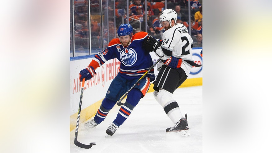 Los Angeles Kings' Derek Forbort (24) vies for the puck with Edmonton Oilers' Leon Draisaitl (29) during second period NHL hockey action in Edmonton, Alberta, on Tuesday, March 28, 2017. (Jason Franson/The Canadian Press via AP)