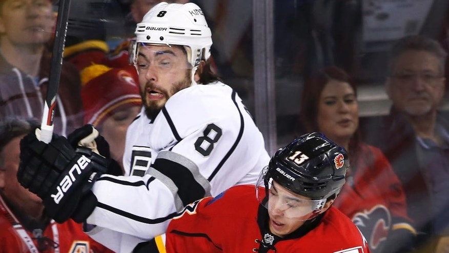 Los Angeles Kings' Drew Doughty, left, is checked into the glass by Calgary Flames' Johnny Gaudreau during the first period of an NHL hockey game in Calgary, Alberta, Wednesday, March 29, 2017. (Larry MacDougal/The Canadian Press via AP)
