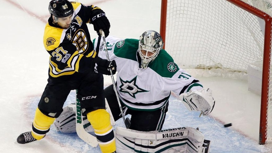 Boston Bruins center Patrice Bergeron (37) shoots wide of the goal as Dallas Stars goalie Antti Niemi (31) defends during the first period of an NHL hockey game, Thursday, March 30, 2017, in Boston. (AP Photo/Elise Amendola, Pool)