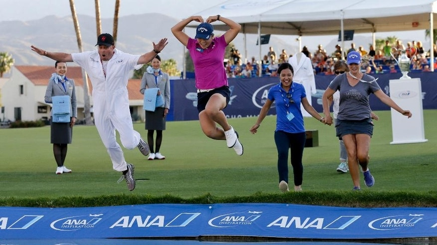 FILE - In this April 3, 2016, file photo, Lydia Ko, of New Zealand, in pink, forms a heart as she jumps into the lake alongside her caddie, Jason Hamilton, left, after winning the LPGA Tour ANA Inspiration golf tournament at Mission Hills Country Club,in Rancho Mirage, Calif. The world's No. 1-ranked player hopes to get back on a winning roll when she returns to the ANA Inspiration this week. By (AP Photo/Gregory Bull, File)