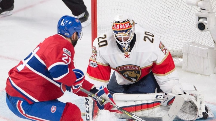 Florida Panthers goalie Reto Berra (20) stops Montreal Canadiens left wing Dwight King (21) during second-period NHL hockey game action in Montreal, Thursday, March 30, 2017. (Ryan Remiorz/The Canadian Press via AP)