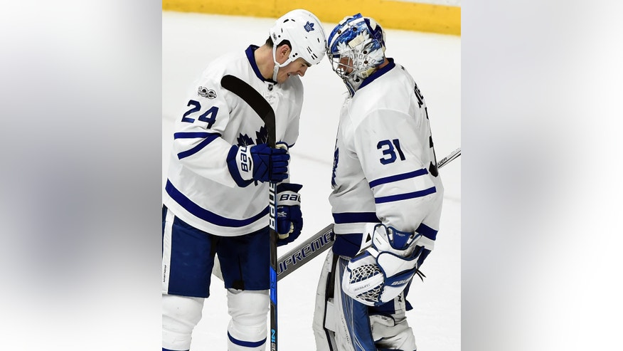 Toronto Maple Leafs center Brian Boyle (24) bump helmets with goalie Frederik Andersen (31), of Denmark, after beating the Nashville Predators in an NHL hockey game Thursday, March 30, 2017, in Nashville, Tenn. (AP Photo/Mark Zaleski)