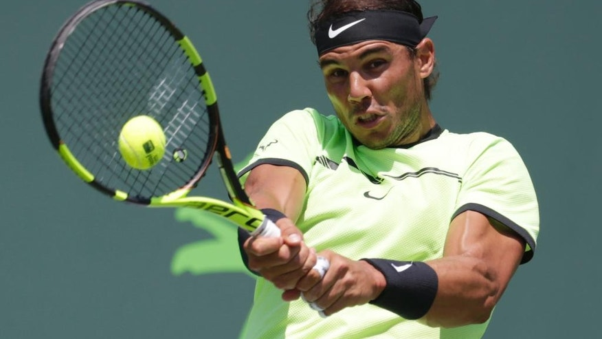 Rafael Nadal, of Spain, hits a return to Fabio Fognini, of Italy, during a men's semifinal match at the Miami Open tennis tournament, Friday, March 31, 2017, in Key Biscayne, Fla. (AP Photo/Lynne Sladky)