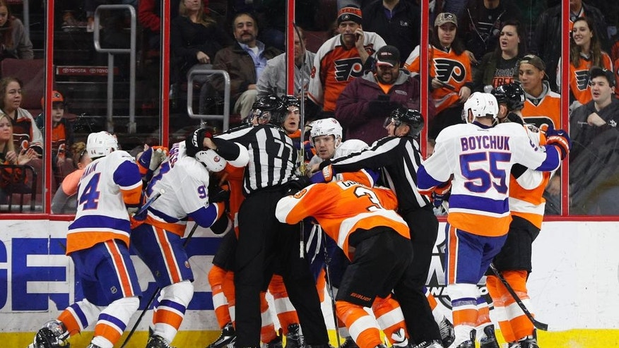 A scrum breaks out between the New York Islanders and the Philadelphia Flyers after the horn blew to end the second period of an NHL hockey game, Thursday, March 30, 2017, in Philadelphia. (AP Photo/Chris Szagola)