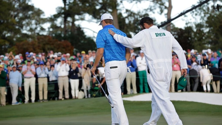 FILE - In this April 10, 2016, file photo, Jordan Spieth is consoled by his caddie Michael Greller on the 18th hole after the final round of the Masters golf tournament in Augusta, Ga. Spieth returns to the Masters after having blown a five-shot lead on the back nine last year. (AP Photo/David J. Phillip, File)