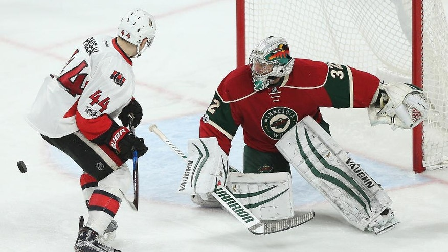 Minnesota Wild's goalie Alex Stalock watches the puck after blocking the goal attempt of Ottawa Senators' Jean-Gabriel Pageau (44) in the third period of an NHL hockey game Thursday, March 30, 2017, in St. Paul, Minn. (AP Photo/Stacy Bengs)