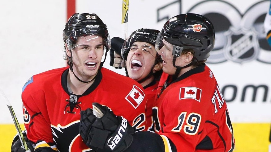 Calgary Flames' Sean Monahan, left, celebrates with Johnny Gaudreau, center, and Matthew Tkachuk after his goal against the San Jose Sharks during the second period of an NHL hockey game Friday, March 31, 2017, in Calgary, Alberta. (Larry MacDougal/The Canadian Press via AP)
