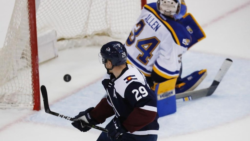 Colorado Avalanche center Nathan MacKinnon, front, looks on as his shot goes past St. Louis Blues goalie Jake Allen for the winning tally during the shootout session of an NHL hockey game Friday, March 31, 2017, in Denver. (AP Photo/David Zalubowski))