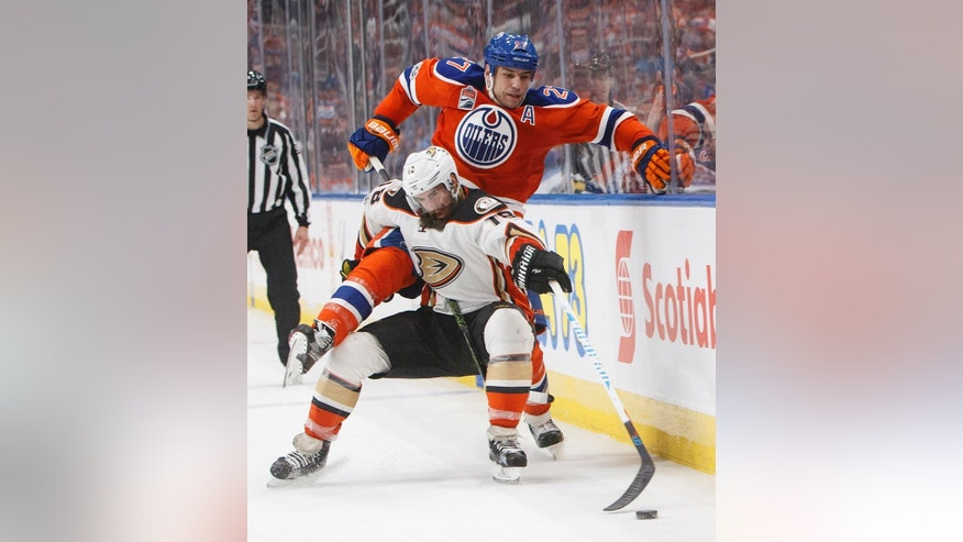 Anaheim Ducks' Patrick Eaves (18) is checked by Edmonton Oilers' Milan Lucic (27) during the third period of an NHL hockey game Saturday, April 1, 2017, in Edmonton, Alberta. (Jason Franson/The Canadian Press via AP)