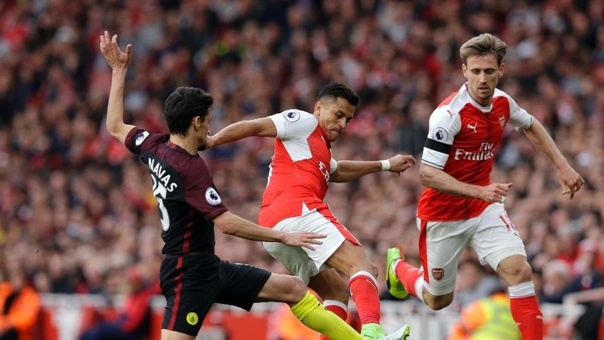 Manchester City's Jesus Navas, left, fights for the ball with Arsenal's Alexis Sanchez during the English Premier League soccer match between Arsenal and Manchester City at the Emirates stadium in London, Sunday, April 2, 2017. (AP Photo/Alastair Grant)