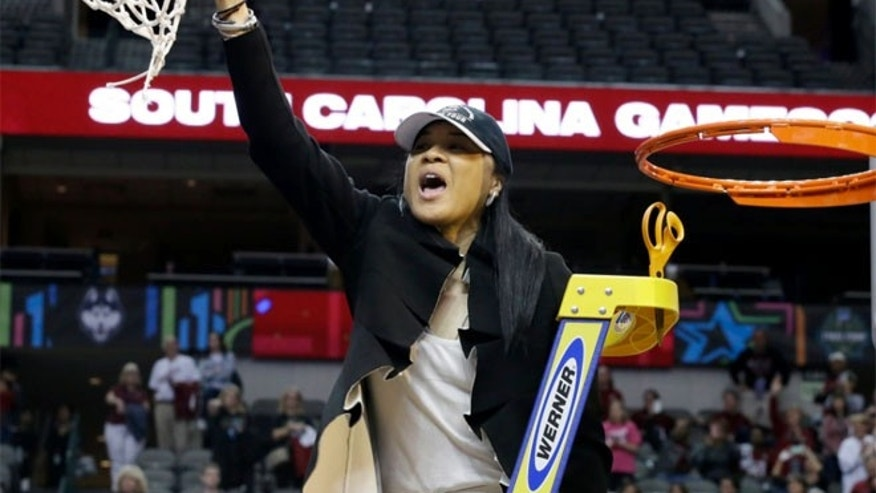 South Carolina coach Dawn Staley cuts down the net as she and the team celebrate their win over Mississippi State in the final of NCAA women's Final Four college basketball tournament