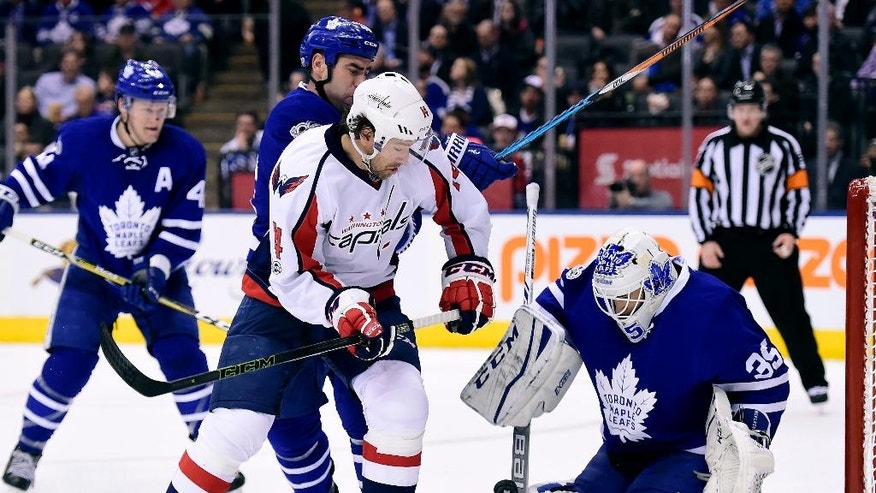 Washington Capitals right wing Justin Williams (14) fails to get the puck into the net as Toronto Maple Leafs goalie Curtis McElhinney (35) defends during the third period of an NHL hockey game Tuesday, April 4, 2017, in Toronto. (Frank Gunn/The Canadian Press via AP)