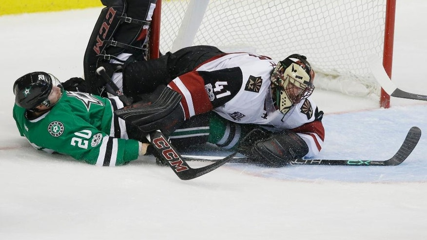 Arizona Coyotes goalie Mike Smith (41) and Dallas Stars center Cody Eakin (20) collide during the third period of an NHL hockey game in Dallas, Tuesday, April 4, 2017. The Stars won 3-2 in overtime. (AP Photo/LM Otero)