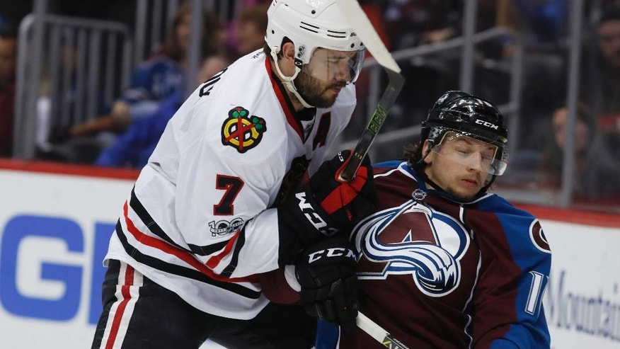 Chicago Blackhawks defenseman Brent Seabrook, left, runs Colorado Avalanche right wing Sven Andrighetto, of Switzerland, into the boards in the first period of an NHL hockey game Tuesday, April 4, 2017, in Denver. (AP Photo/David Zalubowski))