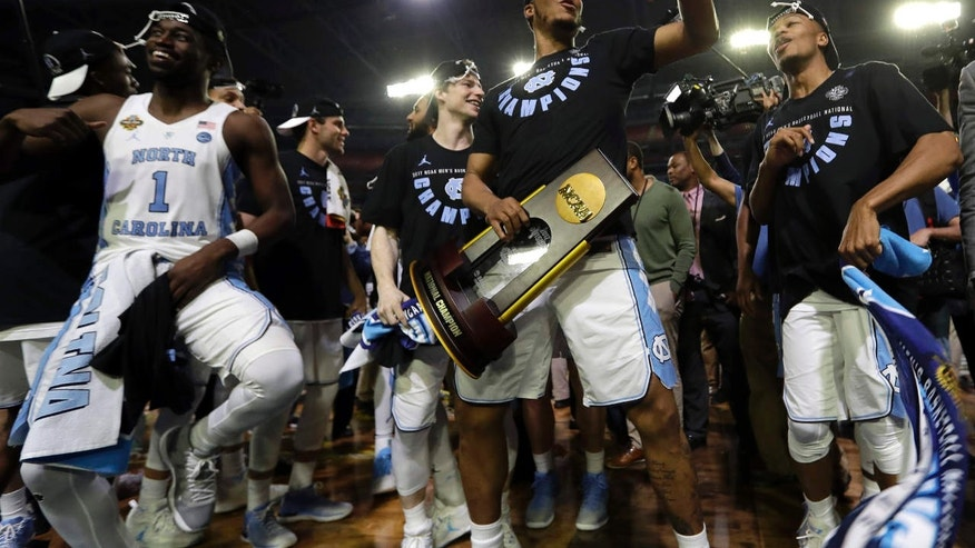 North Carolina's Kennedy Meeks holds the championship trophy as he celebrates with his teammates after the finals of the Final Four NCAA college basketball tournament against Gonzaga, Monday, April 3, 2017, in Glendale, Ariz. North Carolina won 71-65.