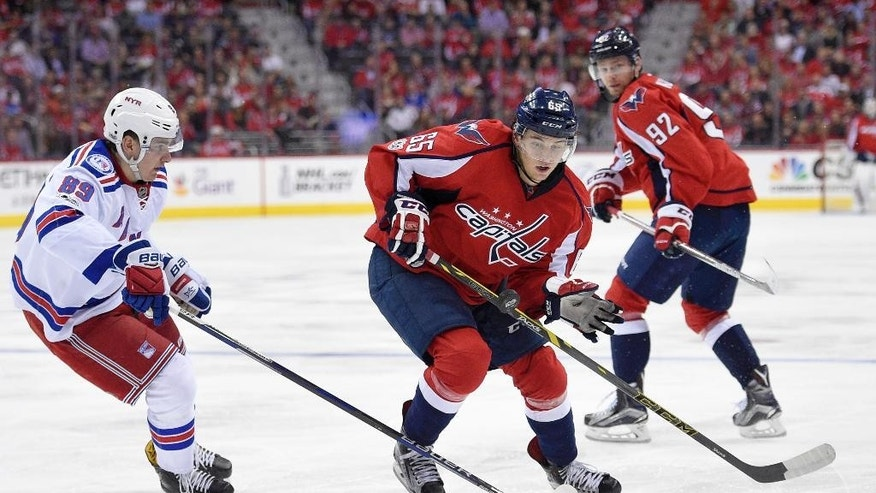 Washington Capitals left wing Andre Burakovsky (65), of Austria, chases the puck against New York Rangers right wing Pavel Buchnevich (89), of Russia, during the second period of an NHL hockey game, Wednesday, April 5, 2017, in Washington. (AP Photo/Nick Wass)