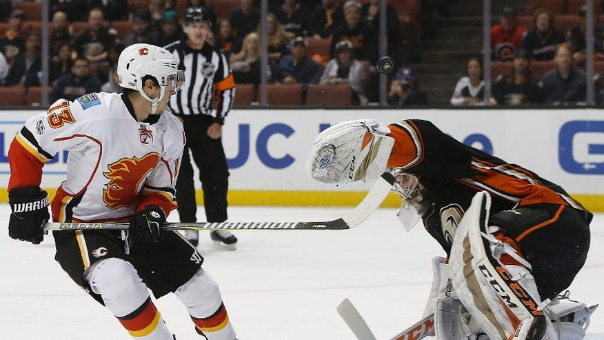 Anaheim Ducks goalie John Gibson, right, deflects a breakaway shot by Calgary Flames left wing Johnny Gaudreau, left, during the first period of an NHL hockey game in Anaheim, Calif., Tuesday, April 4, 2017. (AP Photo/Alex Gallardo)