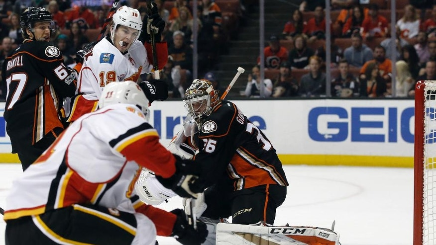 Calgary Flames center Mikael Backlund (11), of Sweden, scores against Anaheim Ducks goalie John Gibson, right, with center Rickard Rakell, left, of Sweden, defending against left wing Matthew Tkachuk (19) during the first period of an NHL hockey game in Anaheim, Calif., Tuesday, April 4, 2017. (AP Photo/Alex Gallardo)