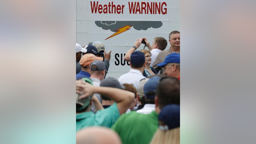 Fans leave Augusta National as a weather warning is posted during a practice round for the Masters golf tournament Wednesday, April 5, 2017, in Augusta, Ga. (AP Photo/Chris Carlson)
