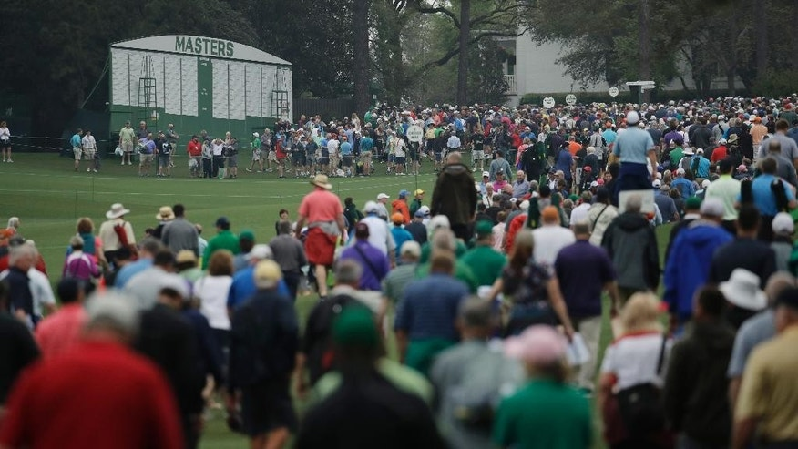Fans leave Augusta National as play is suspended for weather during a practice round for the Masters golf tournament Wednesday, April 5, 2017, in Augusta, Ga. (AP Photo/Charlie Riedel)