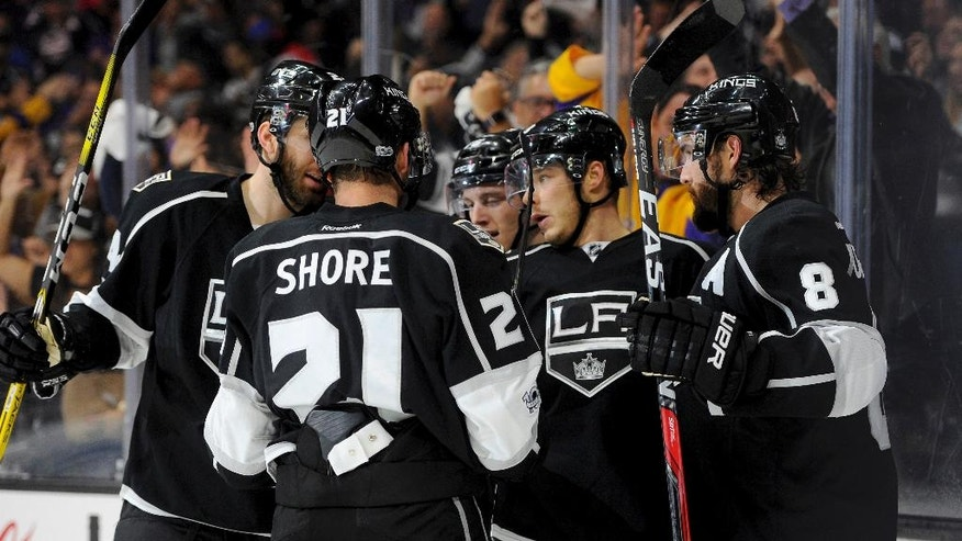 Los Angeles Kings right wing Dustin Brown, second from right, is congratulated by teammates after his second-period goal against the Edmonton Oilers in an NHL hockey game, Tuesday, April 4, 2017, in Los Angeles. (AP Photo/Michael Owen Baker)