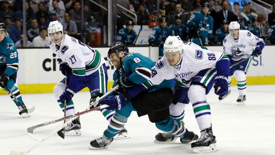 San Jose Sharks' Joe Pavelski, center, is defended by Vancouver Canucks' Nikita Tryamkin (88) during the second period of an NHL hockey game Tuesday, April 4, 2017, in San Jose, Calif. (AP Photo/Marcio Jose Sanchez)