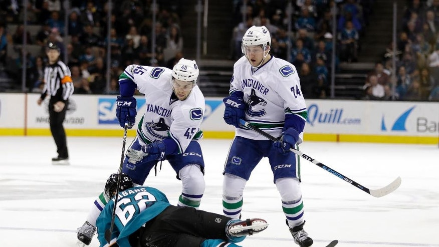 San Jose Sharks right wing Kevin Labanc, bottom, collides with Vancouver Canucks' Michael Chaput (45) and Reid Boucher (24) during the first period of an NHL hockey game Tuesday, April 4, 2017, in San Jose, Calif. (AP Photo/Marcio Jose Sanchez)