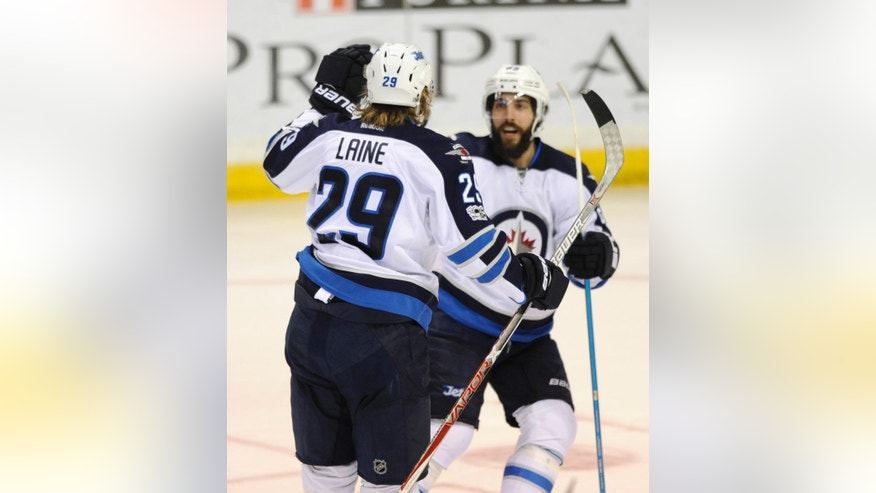 Winnipeg Jets' Patrik Laine (29), of Finland, is congratulated by teammate Mathieu Perreault, right, after his second goal against the St. Louis Blues, during the third period of an NHL hockey game, Tuesday, April 4, 2017, in St. Louis. The Jets won 5-2. (AP Photo/Bill Boyce)