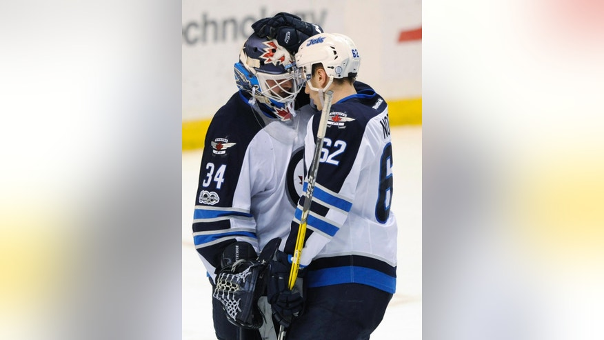 Winnipeg Jets' goalie Michael Hutchison (34) is congratulated by teammate Nelson Nogler (62) after the team's 5-2 victory over the St. Louis Blues in an NHL hockey game, Tuesday, April 4, 2017, in St. Louis. (AP Photo/Bill Boyce)